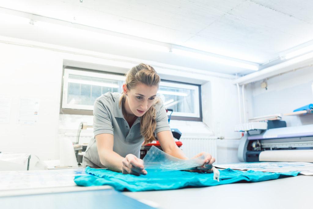 femme qui colle un logo sur t-shirt